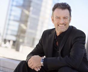 Porträt der lächelnden Geschäftsmann trägt schwarzen Anzug