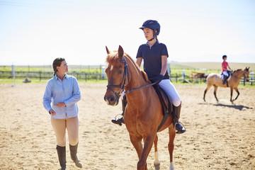 Trainer und Mädchen mit Pferd auf Reitplatz