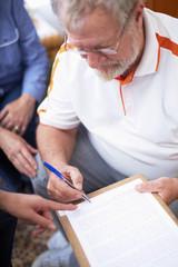 Älterer Mann, der ein Dokument unterzeichnet