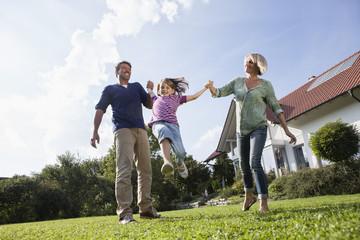 Glückliche Familie, die im Garten spielen