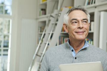 Deutschland, Berlin, älterer Mann mit Tablet-PC, lächelnd