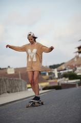 Frankreich, Aquitanien, Seignosse, Frau fährt mit Longboard auf der Straße