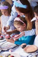 Mädchen garnieren Cupcakes auf eine Geburtstagsparty