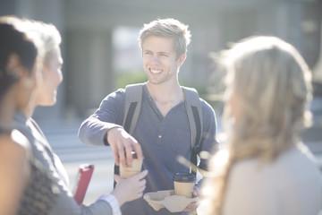 Junger Mann verteilt Kaffee an Freunde