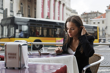 Portugal, Lissabon, Baixa, Rossio, Praca Dom Pedro IV, Teatro Nacional, junge Frau mit Smartphone sitzt im Straßencafé