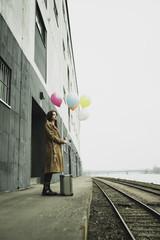 Junge Frau mit Koffer und Ballons auf dem Bahnsteig