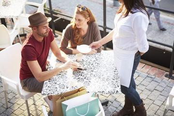 Mann zahlt Rechnung in einem Straßencafé