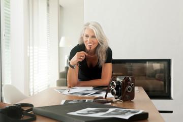 Fotografin mit Fotos und altmodischer Großformat-Kamera auf einem Tisch