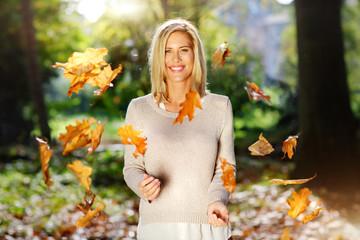 Porträt der lächelnden blonden Frau, wirft mit Herbstlaub