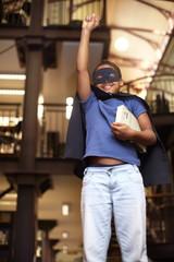 Junge trägt Superhelden-Kostüm in der Bibliothek