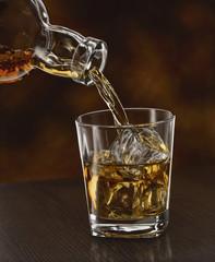 Whisky wird in einWasserglas gegossen, close up