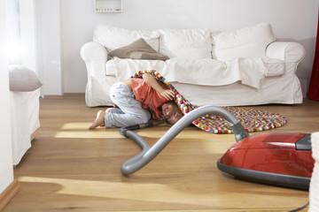 Junge im Wohnzimmer, Staubsaugen unter Teppich