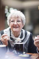Älteren Frau in einem Straßencafé