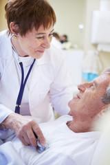 Arzt untersucht älteren Mann im Krankenhausbett