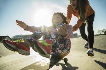 Teenager-Mädchen schiebt Mädchen auf Skateboard