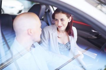 Paar beim Autohändler, Inspiezierung Innenraum eines Autos