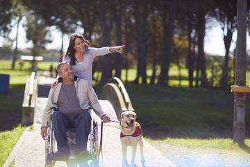Frau mit Mann im Rollstuhl und Hund im Park