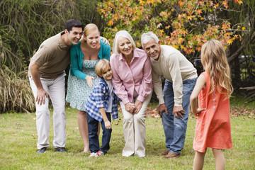 Mädchen macht Foto der Großfamilie im Garten