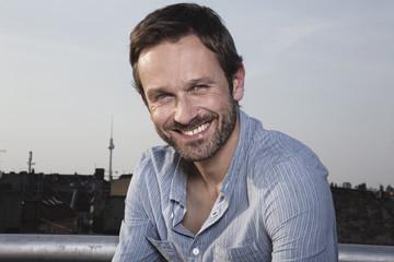 Deutschland, Berlin, Porträt des Mannes auf der Dachterrasse, lächelnd