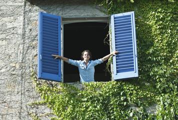 Italien, Toskana, Junger Mann stützt sich auf Fenster mit Fensterläden
