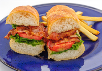 Baguette sandwiches with fried ham on blue plate