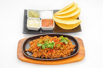 Fried minced beef on hot plate with sauce and crispy flapjacks