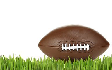 American football on green grass, isolated on white