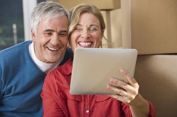 Deutschland, Bayern, Grobenzell, Paar mit Tablet-PC, lächelnd