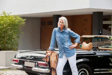 Ältere Frau lehnt an einem Cabrio