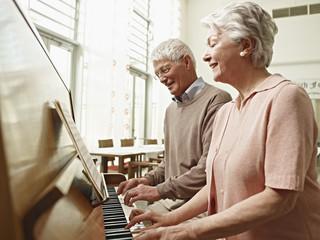 Deutschland, Köln, Seniorenpaar, das Klavier spielt im Pflegeheim