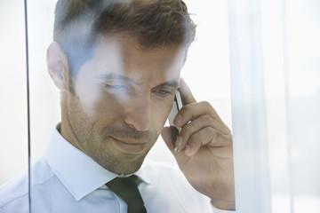 Spanien, Unternehmer am Handy, lächelnd