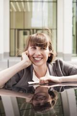 Deutschland, Hessen, Frankfurt am Main, Porträt der lächelnden Geschäftsfrau stützt sich auf Autodach