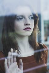 Ernste junge Frau hinter Fensterscheibe
