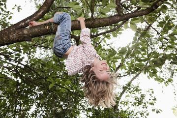 Deutschland, Bayern, München, Mädchen im Baum hängend, lächelnd