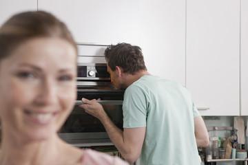 Deutschland, Mann guckt in den Ofen mit Frau lächelnd im Vordergrund