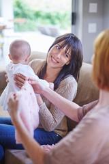 Mutter mit Baby und Freundin, begutachten Baby-Kleidung