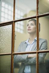 Ernste junge Geschäftsfrau, Blick aus dem Fenster