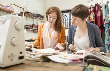 Zwei Modedesignerinnen an ihrem Schreibtisch