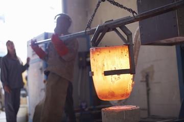 Südafrika, Kapstadt, Gießereiarbeiter schmelzen Bronze