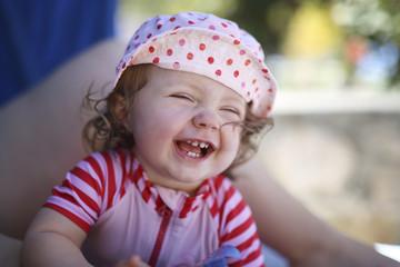 Portrait des lachenden Baby auf dem Schoß der Mutter