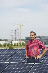 Deutschland, München, Älterer Mann steht in Solaranlage, Lächeln, Portrait