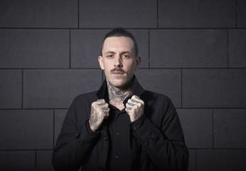 Porträt von Mann mit Tätowierungen auf seinen Händen und seinem Hals