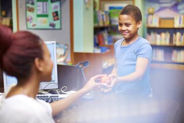 Bibliothekar gibt dem Jungen ein Apfel