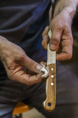 Messermacher reibt Leinöl auf Messergriff