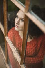 Junge Frau schaut aus dem Fenster