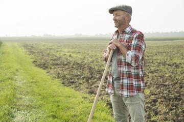 Bauer steht vor einem Feld