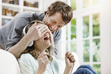Deutschland, Hessen, Frankfurt am Main, Erwachsenes Paar zu Hause, Musik hören