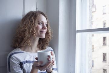Deutschland, Bayern, München, junge Frau schaut aus dem Fenster, lächelnd