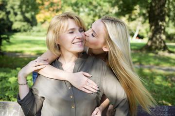 Erwachsene Tochter küsst Mutter im Park