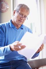 Älterer Mann studiert ein Dokument
